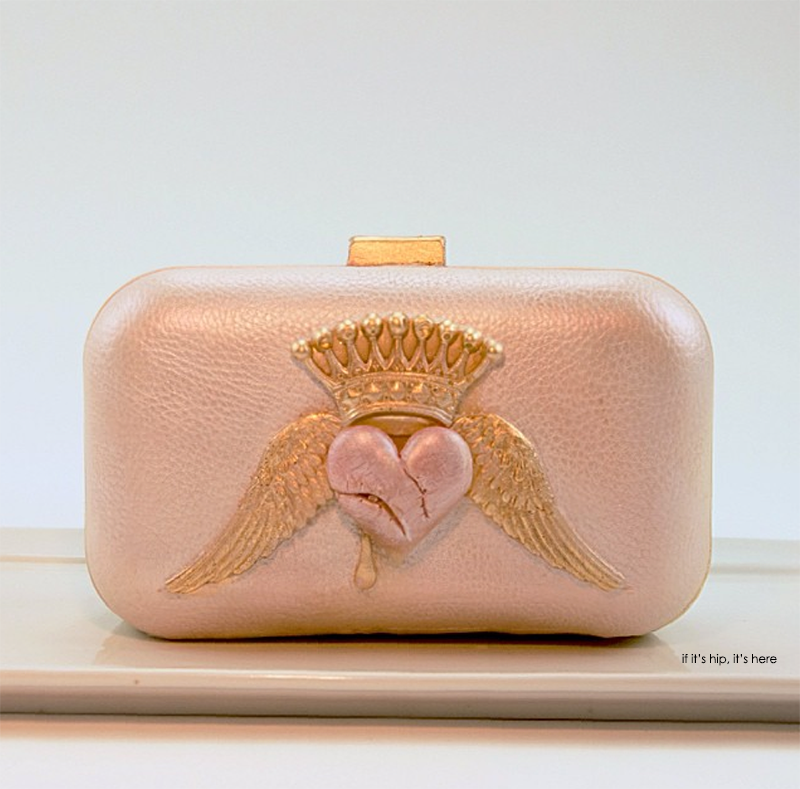 White chocolate clutch with pink heart, gold wings and crown. Sweetheart chocolate purse is hand painted with edible lustre dusts and filled with moist red velvet cake