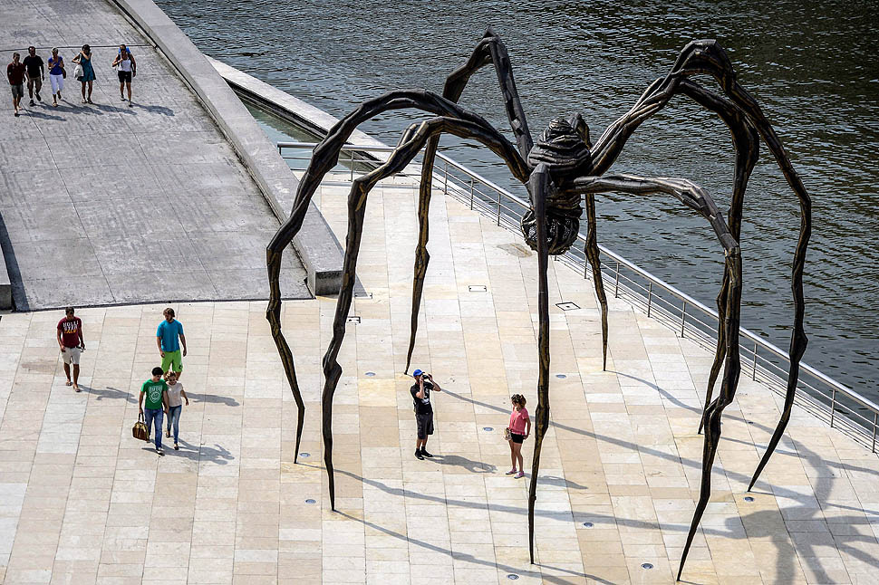 """Pedestrians pass the """"Spider Maman"""" steel sculpture by Louise Bourgeois on the waterside in Bilbao, Spain."""