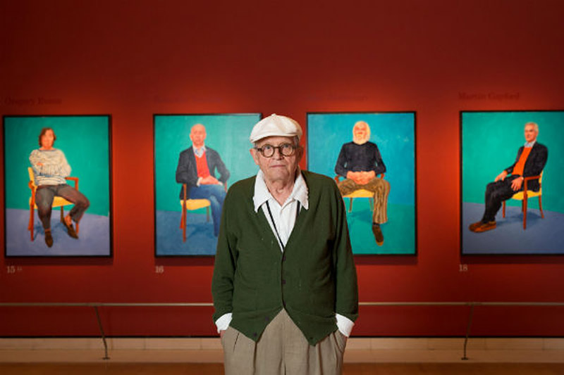 David Hockney stands in front of some of his 82 portraits, photo by David Parry